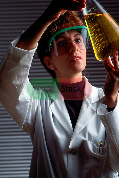 woman scientist wearing face shield looking at yellow liquid in large glass beaker