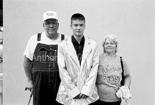 Memphis, Tennessee<br /> USA<br /> August 12, 2002<br /> <br /> 16 year old, Justin Miller, will perform his imitation of Elvis at a tent near Graceland. His parents Earl (left) and Nelle drove him from their home town of Jamestown, Tennessee. They are in Memphis to attend the 25th anniversary of Elvis Presley's death.