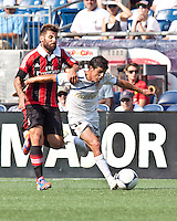 Olimpia forward Ramio Bruschi (33) holds off AC Milan midfielder Antonio Nocerino (8) in a tackle.  AC Milan defeated Olimpia 3-1 at Gillette Stadium on August 4, 2012
