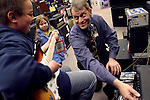 """WATERBURY, CT - 23 March 2004 - 032304TH10 - Bruce """"The Juice"""" Johnson, one of the guitar experts at the Guitar Center in Manchester, shows Brett Burns, 11, and his sister, Jackie, 7, of Manchester one of the amplifiers in the store Tuesday night.     TODD HOUGAS PHOTO"""
