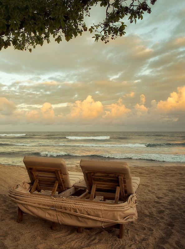 Sunrise and waves with beach chairs. Hawaii, The big Island.