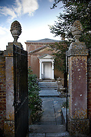 A gateway topped by two stone pine cones leads to a Grecian styled building in the grounds