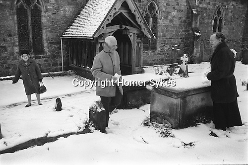 Hartfield Dole, Nicholas Smith bequest. Easter Good Friday at the Church of St Mary the Virgin Hartfield Sussex Uk 1975.  <br /> <br /> The graveside dole takes place at the grave of Nicholas Smith who died in 1631. In his will he left money that was to be invested and the interest to be divided between the poor of the parish on Good Friday.  Smith was a rich resident of East Grinstead, who went around the parish dressed as a tramp begging wherever he could for food and shelter. He was treated with contempt everywhere and sent on his way, apart from in Hartfield, where he was treated with generosity and compassion.<br /> <br /> In his will he stipulated that he should be buried in Hartfield and a charity set up bearing his name.<br /> <br /> In 1975 two parishioners claimed the dole.<br /> Parishioners receive the bequest from Rev'd Lawrence Dykes