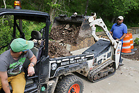 Dave Laney, maintenance equipment operator with the Rogers Parks Department, (from left) waits for Jason Kilby to load debris into a vehicle, Monday, May 3, 2021 at Lake Atalanta in Rogers. The Rogers Parks Department has been clearing debris from Lake Atalanta since last week's flooding. Flood water scattered large pieces of tree trunks and rocks along with miscellaneous items like trash and tires along the Lake Atalanta grounds closing the pavilion. The parks department is moving the debris to a side of the parking lot in preparation for FEMA who may provide funding to remove it. The parks department hopes to open the pavilion again by Tuesday. Check out nwaonline.com/210504Daily/ for today's photo gallery. <br /> (NWA Democrat-Gazette/Charlie Kaijo)