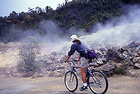 Bicyclist pedals by sulphur vents at Volcanoes National Park.
