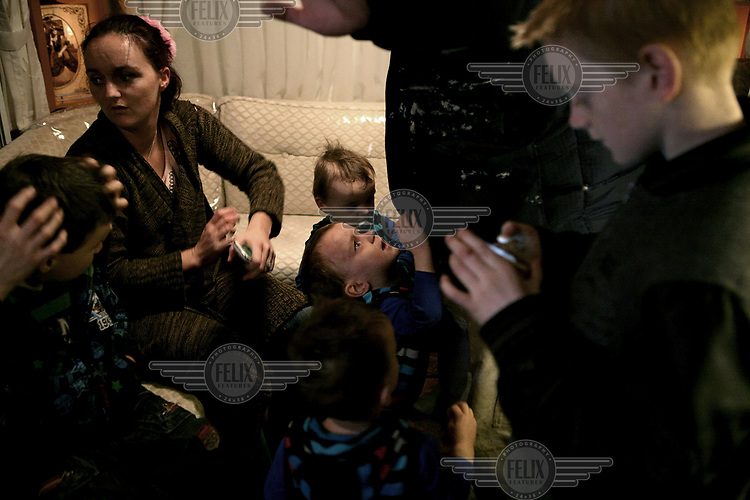 David Sheridan cries for attention in his family's busy trailer where numerous aunts, uncles and cousins have all gathered together to celebrate Christmas, at Dale Farm, an Irish Travellers' site on a former scrapyard in Essex.