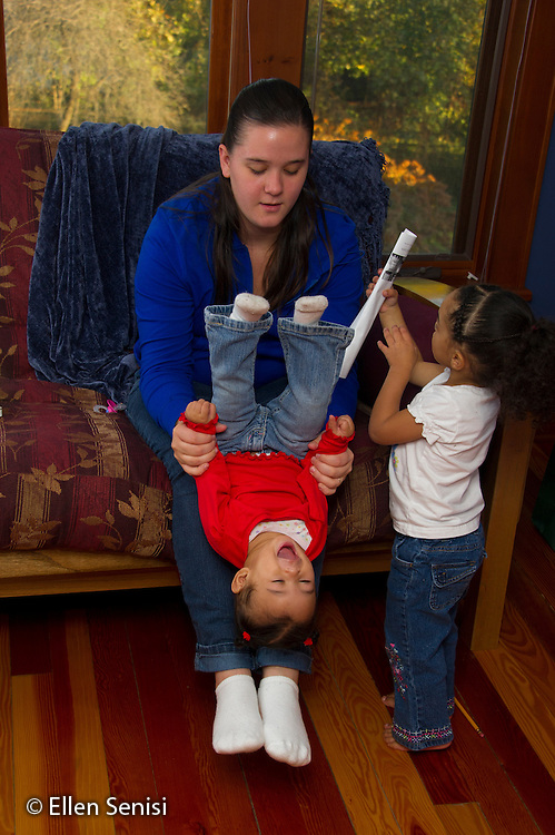 MR / Schenectady, NY. Mother (21) plays with her infant daughter (11 months, African American & Caucasian) by tipping her upside down. Her older daughter (2, African American & Caucasian) tries to get her attention. MR: Dal4, Dal6, Dal5. ID: AL-HD. © Ellen B. Senisi