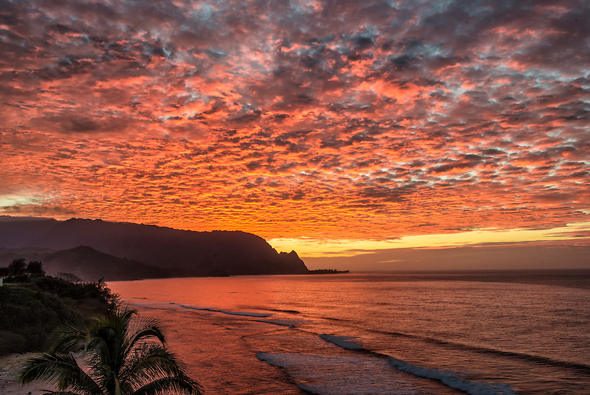 A spectacular array of bright red-orange clouds appears after the sun goes down behind Bali Hai (Mount Makana) on the north shore of Kauai.