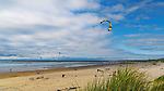 Kiteboarding, Dunes, grass, blue sky mark the pacific ocean beach at South Beach State Park, Newport, Oregon