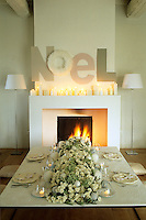 A large flower arrangement dominates the simply laid table in this living room decorated for Christmas