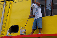 Worker painting the wall at a House view from the car window Manila, Philippines