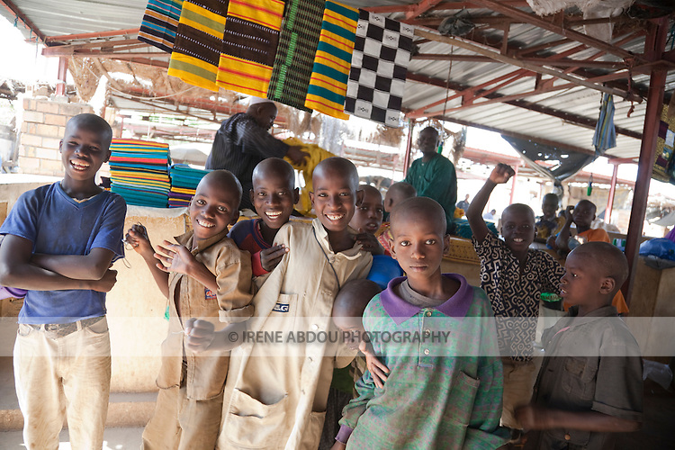 Fulani children pose in front of a market stall selling colorful woven blankets in Segou, Mali.