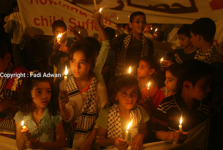 """Palestinian children hold candles during a demonstration organized by civilians protesting against Israeli sanctions on the Gaza Strip, in front of the United Nation headquarters in Gaza City, Thursday, Nov. 1, 2007. Earlier this week, Israel's attorney general held up the government's plan to cut back electricity supplies to Gaza, demanding more work be done to prevent humanitarian harm. Palestinians in Gaza rely on Israel for all of their fuel and more than half of their electricity.""""photo by Fady Adwan"""""""