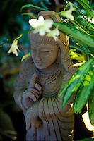 Kwan yin stone statue with orchids at Paleaku gardens, South Kona, Big island