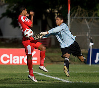 Sandy Sanchez (1) of Cuba punches the ball as Jorman Aguilar (18) of Panama  closes in during the group stage of the CONCACAF Men's Under 17 Championship at Jarrett Park in Montego Bay, Jamaica. Panama tied Cuba, 0-0.