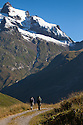 Hikers walking along track up into mountains on the Tour de Mont Blanc long distance footpath. French Alps, France.