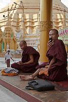 Myanmar, Burma.  Shwedagon Pagoda, Yangon, Rangoon.  Two Buddhist Monks with Cell Phones.