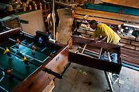 Fabian R., a carpentry worker, polishes the wooden case with a fine sandpaper at a table football workshop in Quito, Ecuador, 3 March 2012. Table football, also known as futbolin in Latin America, is a widely popular table-top game in Ecuador. During the annual fairs, the rusty old outdoor-designed tables, fully ocuppied by excited children, may be found on all public places, particularly on the squares and in the parks. Although there have always been several small table football workshops in all large Ecuadorean towns, the table football craft and tradition is on a decline in last years, mainly due to the video-game boom.