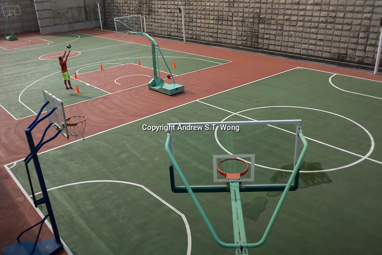 A Chinese youth plays basketball outside the Dongguan Youth Activities Centre in Dongguan, Guangdong province, China, August 2016.