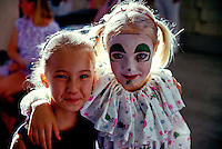 "Two young girls, one wearing a clown costume, smile at the """"First Night"""" event on Oahu."