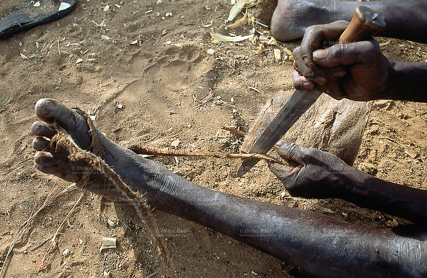 Sudan. West Darfur. Kerenek. An old man is cutting with a knife the dry skin of a dead cow to use it as a leather rope. © 2004 Didier Ruef