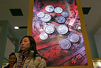 Visitors stand by a big light box of Chinese currency yuan during an exhibition about finance knowledge at the National Museum of China in Beijing, China. .