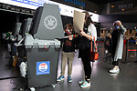 BROOKLYN, NY — OCTOBER 24, 2020:  A child wearing a face mask scan a ballot inside the Barclay's Center, during the first day of early voting in the U.S. Presidential Election, on October 24, 2020 in Brooklyn, NY.  Photograph by Michael Nagle