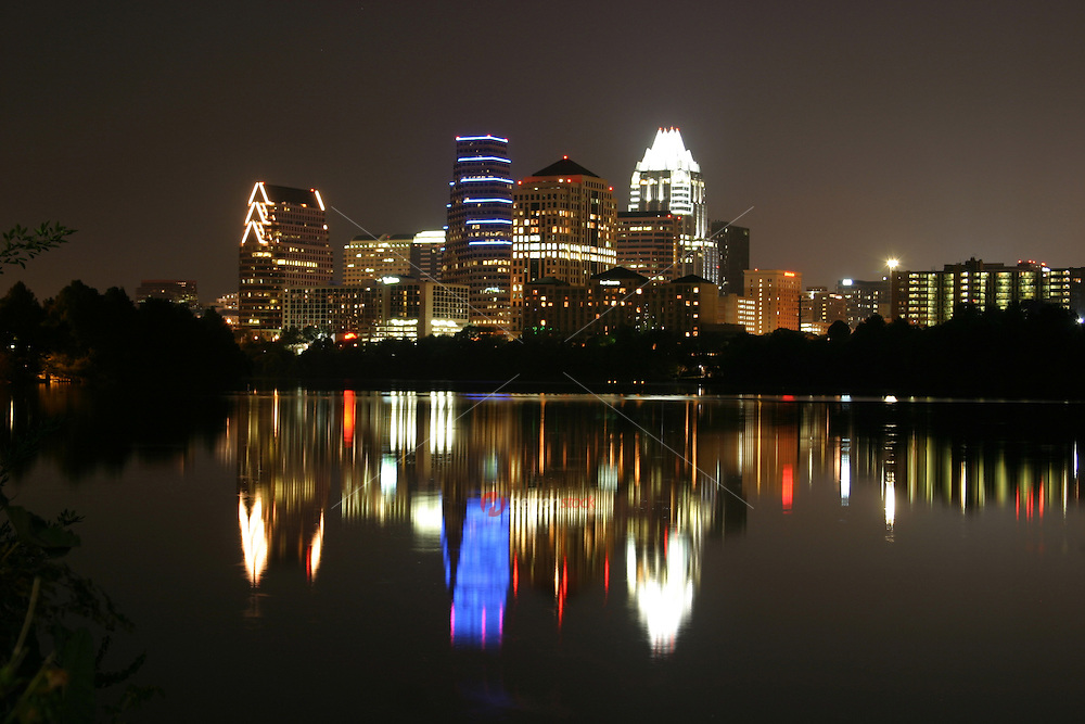 Austin, Texas downtown night city skyline with lights reflecting on the calm water of Townlake in Austin, Texas, USA