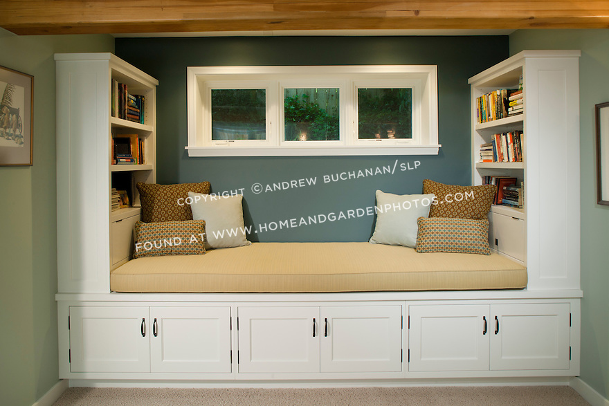A roomy window seat bench offers a cozy space for reading, while the built-in bookshelves and cupboards surrounding it provide ample storage in this newly-remodeled basement.