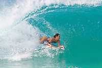 Woman bodyboarder pulls into a clean barrel at rock piles surf break on the north shore of Oahu.