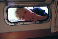 Young blond boy laughing and looking in a porthole aboard sailing yacht 'Heron'