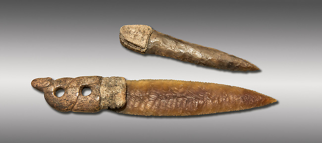Brown obsidian dagger with a bone handle carved into the shape of a snake. It is believed this may have been a ritual dagger. Catalhoyuk Collections. Museum of Anatolian Civilisations, Ankara. Against a grey background