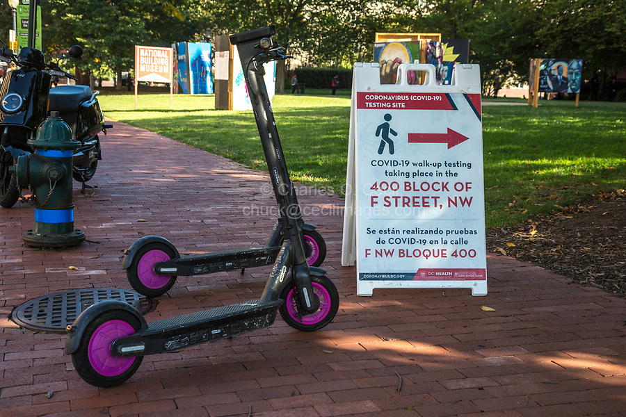 COVID-19 Testing Site Bilingual Sign and Rental Electric Scooters, Washington DC, USA, October 2020.