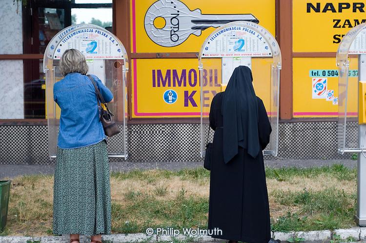 A nun uses a public telephone kiosk in Lublin.