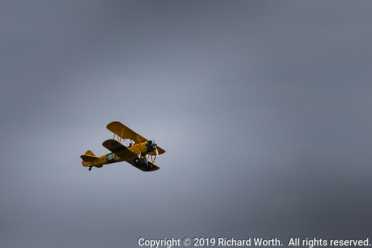 A yellow biplane circles the sky over the Duck Pond community park in San Lorenzo, California near San Francisco Bay.
