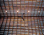 The roof of the refurbished barn features exposed rafters and slats with insulation and roofing above.  (Inside the refurbished barn at Sunset Hills Vineyard and Winery, Purcellville VA.)