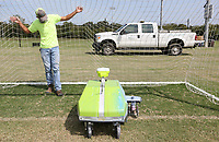 Jose Hernandez, with the city of Fayetteville's Parks and Recreation Department, monitors the robotic line painter, Turf Tank, as it is recalibrated Monday, September 14, 2020, for the correct size of soccer net on one of the fields at Kessler Mountain Regional Park in Fayetteville. The robot is currently being used to outline 42 soccer fields that are within the city at Walker, Lewis and Kessler Mountain Regional Park. Check out nwaonline.com/200915Daily/ and nwadg.com/photos for a photo gallery.<br /> (NWA Democrat-Gazette/David Gottschalk)