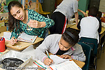 Public elementary school grade 4 class with science specialist two girls working together on experiment horizontal