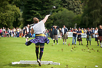 A competitor wearing a kilt throws a putting ball in an event at the Inveraray Highland Games, held at Inveraray Castle in Argyll.