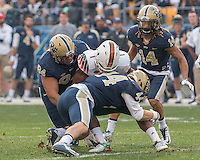 Pitt defensive lineman Jeremiah Taleni (94) and linebacker Matt Steinbeck (44) tackle Miami running back Mark Walton (1). The Miami Hurricanes football team defeated the Pitt Panthers 29-24 on  Friday, November 27, 2015 at Heinz Field, Pittsburgh, Pennsylvania.