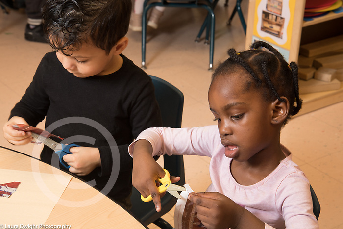 Eucation Preschool 3 year olds boy and girl sitting side by side using scissors to cut paper