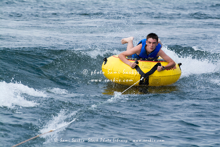 Boy riding an inflatable seabiscuit in the sea, Biscarrosse, France.