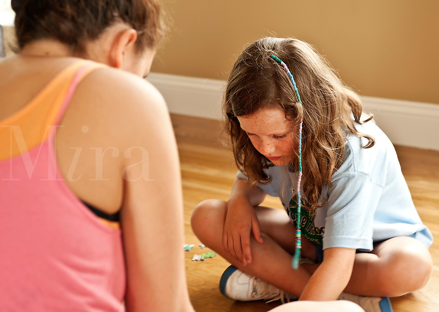 Girls putting together a puzzle.