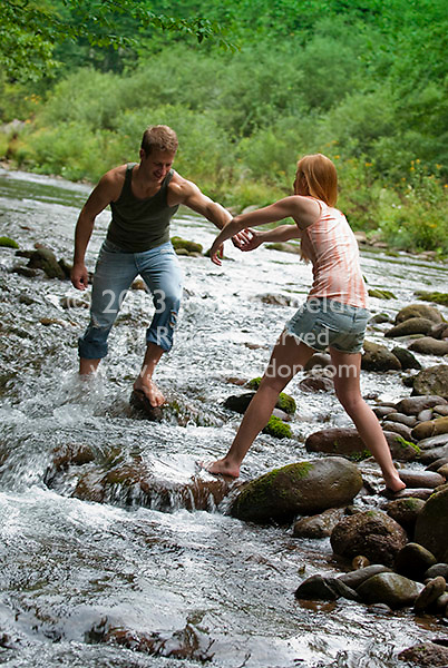 Young couple helping each other over stream