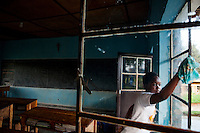 """The classroom at Nyange Secondary School where six students were killed in 1997 during a cross border attack. The attackers told the students, gathered in a late night study session, to separate themselvesa s Hutu and Tutsi. When the students refused asnwering that they were Rwandans not Hutu or Tutsi  they were killed. They are memorialized on the school grounds and beyond as national Heroes. """"If I could  speak to them today I would tell them that they are national heros. That the goverment policy of One Rwanda is the same as thier message of courage before thier killers."""" - Vincent Nsanza school teacher and prefect of discipline. Photo by Brendan bannon. Nyange, Rwanda. Feb 28, 2014"""