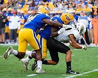 Pitt defensive linemen Patrick Jones (91) and Deslin Alexandre (5) tackle UCF quarterback Dillon Gabriel. The Pitt Panthers defeated the UCF Knights 35-34 in a football game played at Heinz Field, Pittsburgh, Pennsylvania on September 21, 2019.