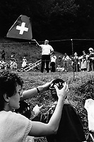 Switzerland. Canton Uri. Rütli. 1 August 1990. Swiss national holiday. Public holiday. A man throws a swiss flag in the air. Other men play the traditional Alp horn. The alphorn or alpenhorn or alpine horn is a labrophone, consisting of a wooden natural horn of conical bore, having a wooden cup-shaped mouthpiece, used by mountain dwellers in the Swiss Alps. A group of women wear national traditional costumes. A mother puts on her son's head a hat with edelweiss flowers. Rütli (or Grütli in French) is a mountain meadow in the Seelisberg municipality of the Swiss canton of Uri. Here the oath of the Rütlischwur is said to have occurred, the legendary turning-point in the pursuit of independence. Every August 1, on the Swiss National Day, the oath is re-enacted to commemorate the forming of the Old Swiss Confederacy. Rütli is the birthplace of the Swiss Confederation. The flag of Switzerland displays a white cross in the centre of a square red field. The white cross is known as the Swiss cross. © 1990 Didier Ruef
