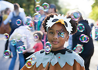 African-American Girl dressed in eagle outfit, surrounded by bubbles, Arts A Glow Festival, Burien, WA, USA.