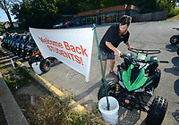 Garrett Adams, operations manager for Scoot Tribe, places an all-terrain vehicle against a bucket Tuesday, Sept. 7, 2021, to secure a sign welcoming back University of Arkansas students as he prepares for the day at the scooter and motorsports store in Fayetteville. The store offers scooters, motorcycles and ATVs for sale and provides service. Visit nwaonline.com/210908Daily/ for today's photo gallery.<br /> (NWA Democrat-Gazette/Andy Shupe)
