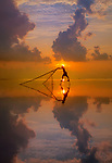 Good morning Vietnam - fishermen on bamboo stilts try to make a catch with nets against a glorious sunrise.  They are around ten kilometres from shore and use their hand-made nets, made with two longer bamboo sticks, to scoop up fish and shrimp from the shallow water.<br /> <br /> The stillness of the surface of the water gives it a serene, mirror-like appearance.  These photographs were taken by Nguyen Quy on Quang Lang Beach, in the province of Thai Binh, Vietnam.  SEE OUR COPY FOR DETAILS.<br /> <br /> Please byline: Nguyen Thi Quy/Solent News<br /> <br /> © Nguyen Thi Quy/Solent News & Photo Agency<br /> UK +44 (0) 2380 458800